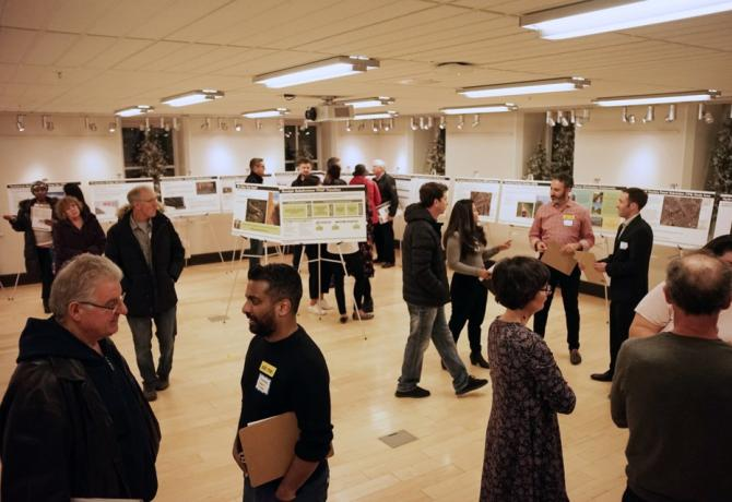 Picture of people talking and viewing information boards at an open house