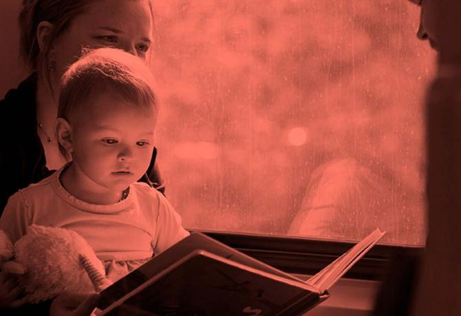 Picture of a young person reading next to a window