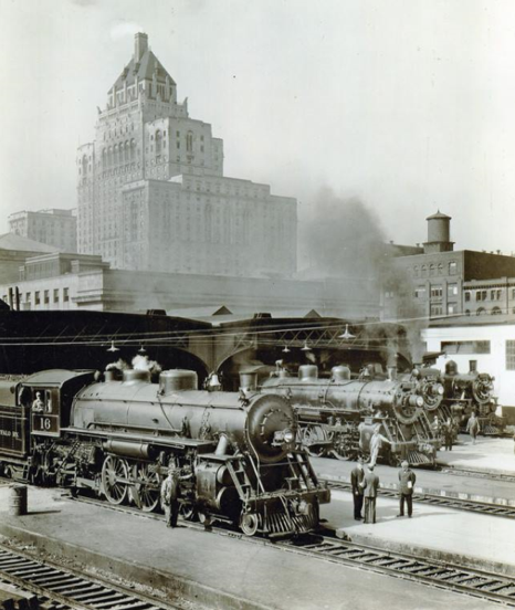 An iconic image of Toronto Union Station from 1930, showing four steam engines just outside the train shed and the Royal York Hotel towering above in the background.